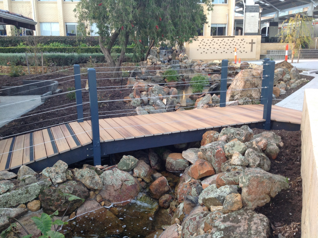 wooden bridge over creek at Mazenod College by Landscapes For Life